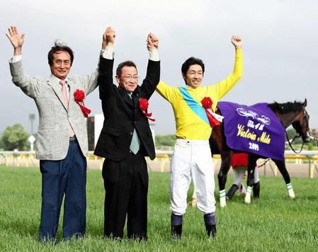 2009年5月17日ヴィクトリアマイルをウオッカで制し、手を挙げる角居師(中央、左は谷水オーナー、右は武豊)