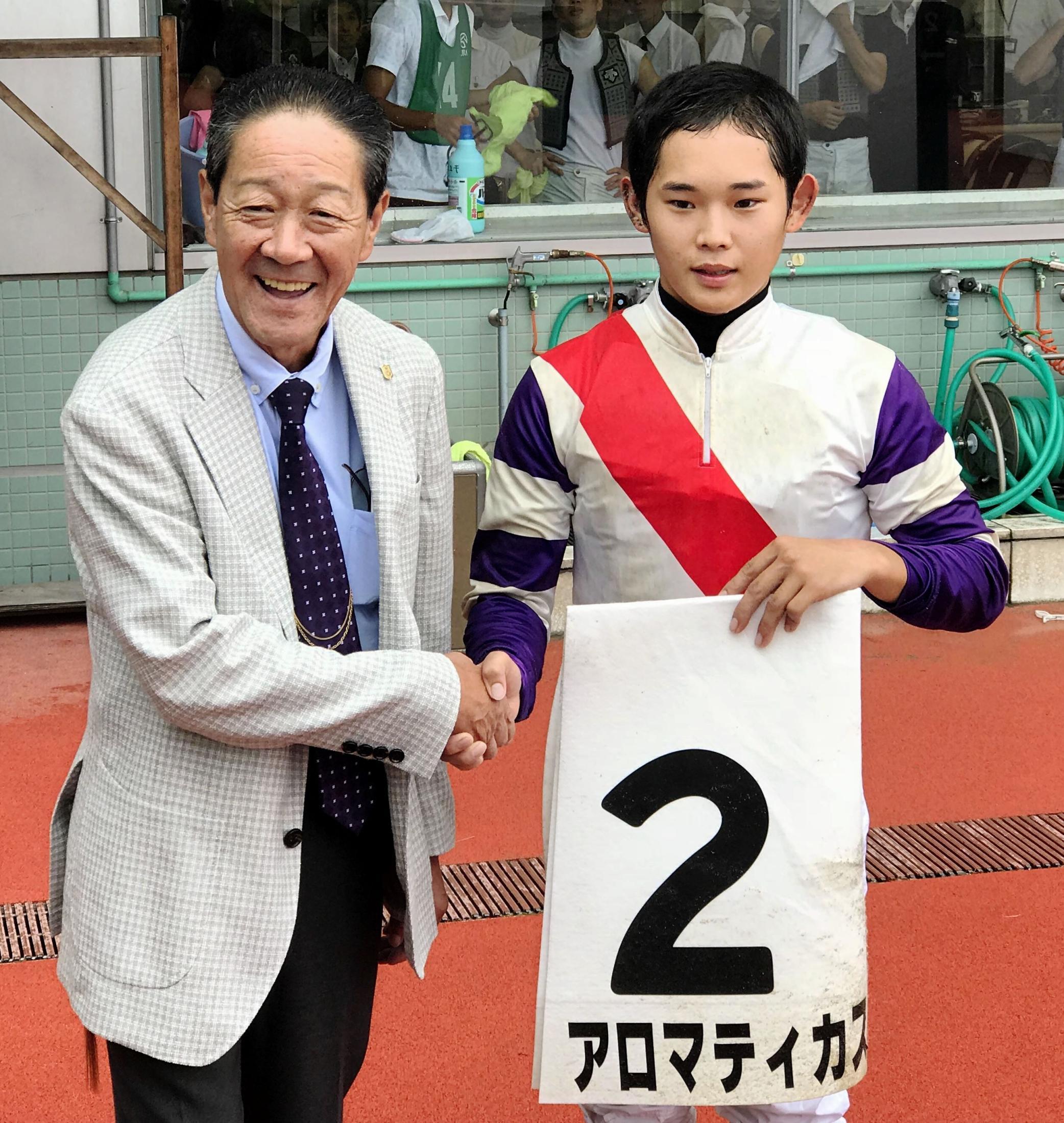 JRA初勝利を挙げ、湯窪師(左)と握手を交わす服部