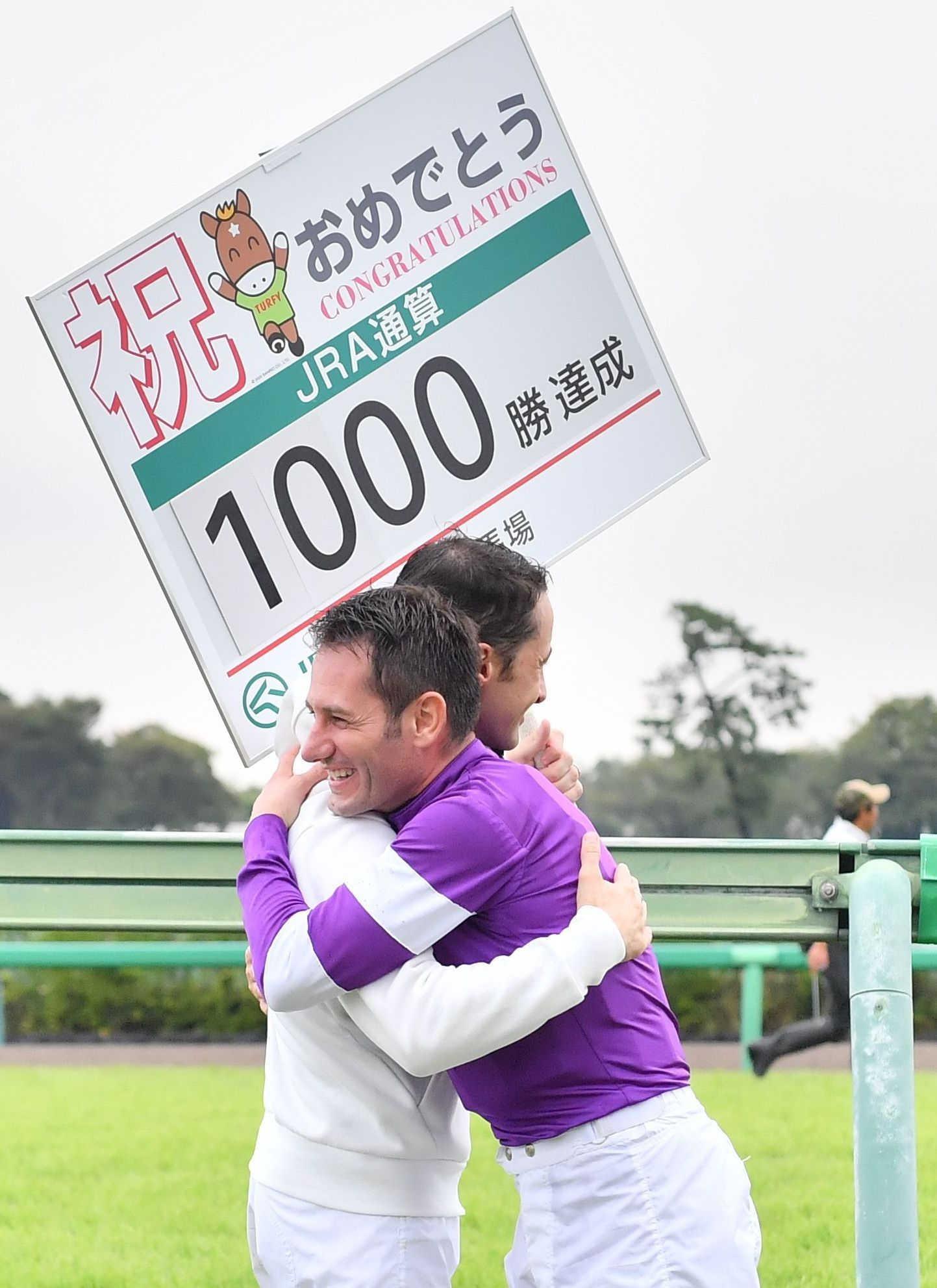 JRA通算1000勝を達成し、ルメール(左)と抱き合って喜ぶM・デムーロ