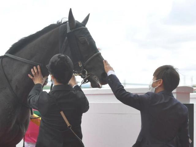 厩舎初出走のテイエムジャガーをねぎらう四位師(右)=阪神競馬場(撮影・石湯恒介)