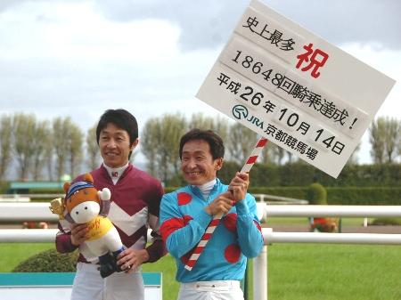 JRA通算最多騎乗数記録を9年ぶりに更新した武豊騎手とプラカードを持つ横山典弘騎手 (c)netkeiba.com